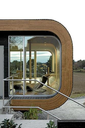 BØLGET: Det bøyde treet gir huset visuell ro. Hvit Bahnsen hvilestol tegnet av arkitekt Jørn Utzon. Eikematerialer fra Øydna Bruk i Lyngdal.