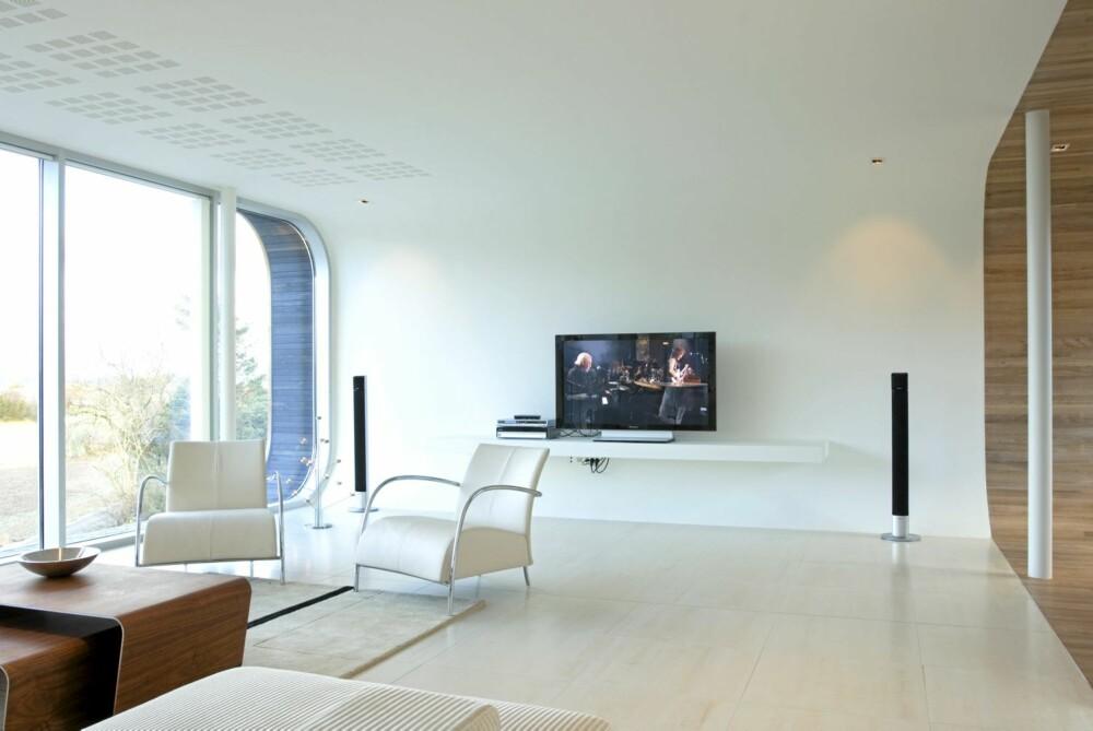EN KRITTHVIT VERDEN: Hovedetasjen på hundre kvadratmeter er oppsiktsvekkende ren og lys - og med buet bakvegg. En egen hylle for tv stikker rett ut fra den bøyde veggen.