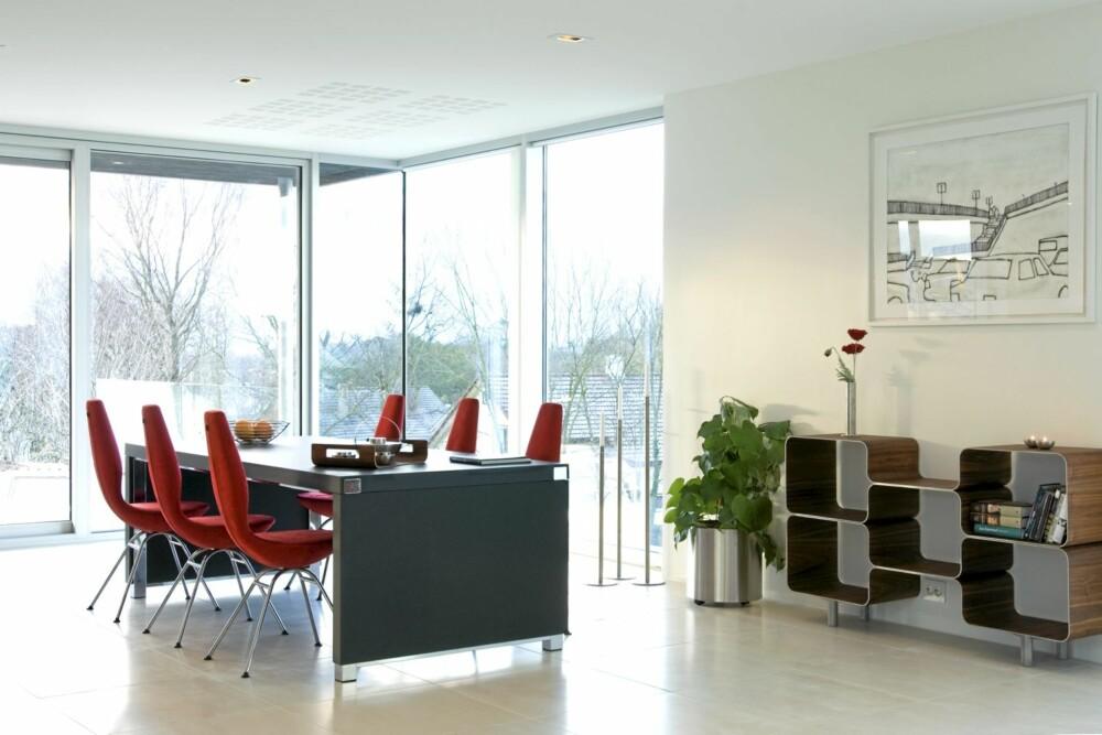 ET HUS MED SONER: Stuen ligger i forkant av kjøkkenet og åpner seg mot utsikten. Knallrøde Date stoler fra Varier.