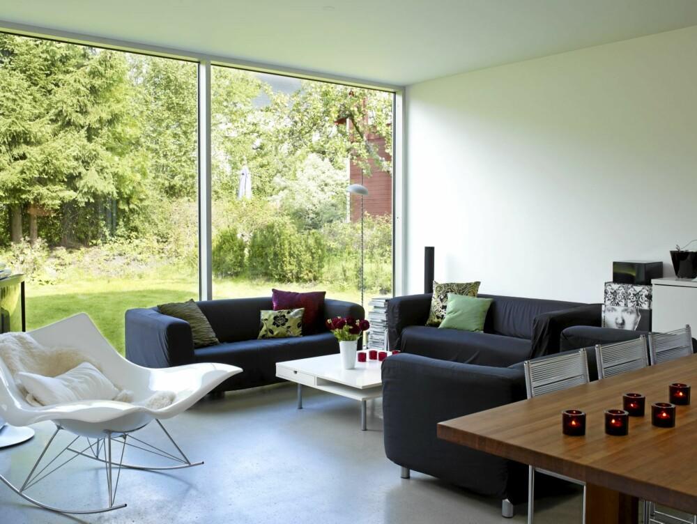 """GRØNN UTSIKT. Stuen har utsikt mot hagen som ligger i skogkanten. Det solide spisebordet i eik er tegnet av Christine. Salonggruppen består av tre """"Klippan""""-sofaer fra Ikea som har skiftet trekk noen ganger."""