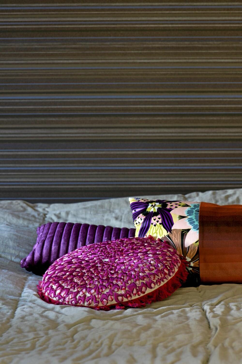 KREATIVT SAMSPILL: Det oppsiktsvekkende Elitis-tapetet fungerer fint sammen med et fløyel sengeteppet og fargeglade, skinnende puter.