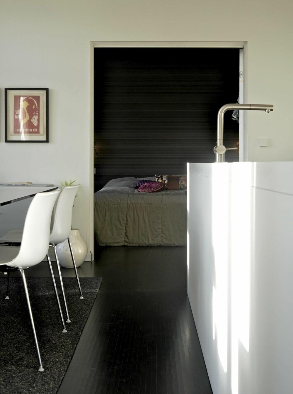 RETT MOT SOVEROMMET: Her ser du hvordan kjøkkenet danner midtpunktet i leiligheten, og at soverommet ligger i den ene enden av rekken av rom. Catifa spisestuestoler fra italienske Arper. Et mørkbeiset tregulv og en renskåren portal inn til soveværelset matsjer hverandre.