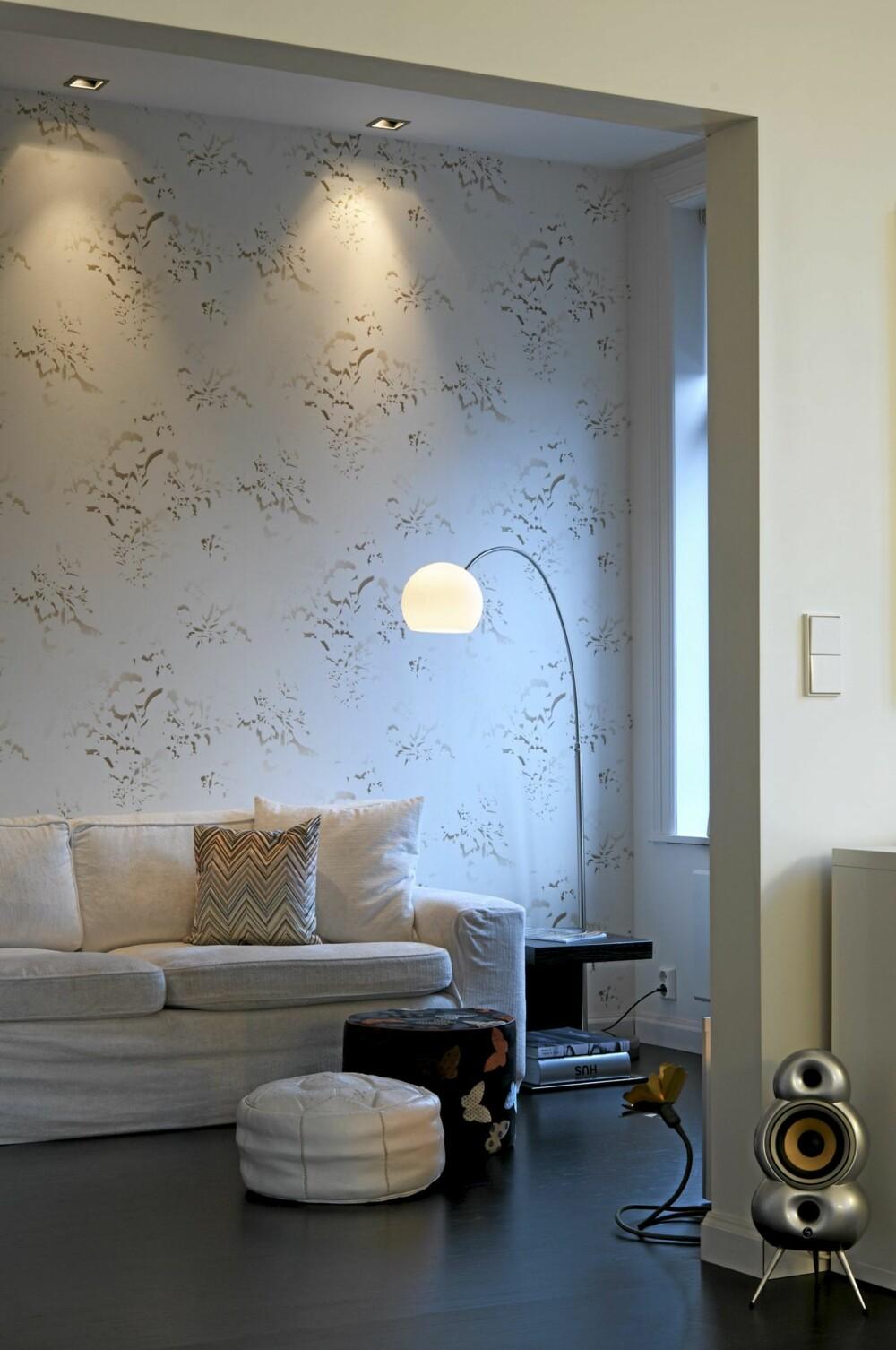 AVSLAPPET SONE: Tv-stuen ligger i direkte forlengelse av hjørnestuen. Bakveggen prydes av et akvarellaktig  Elitis-tapet. En gammel Ikea-sofa - en utstillingsmodell kjøpt i en London-butikk ble forynget med et nytt trekk og Missoni-puter. Kasthall mosaikk tregulv.