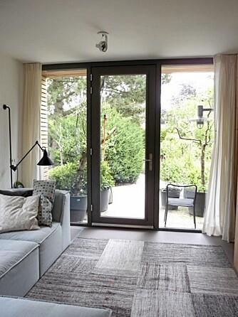 TERRASSE: Fra stuen går det en terrasse ut til en frodig uteplass med hage.