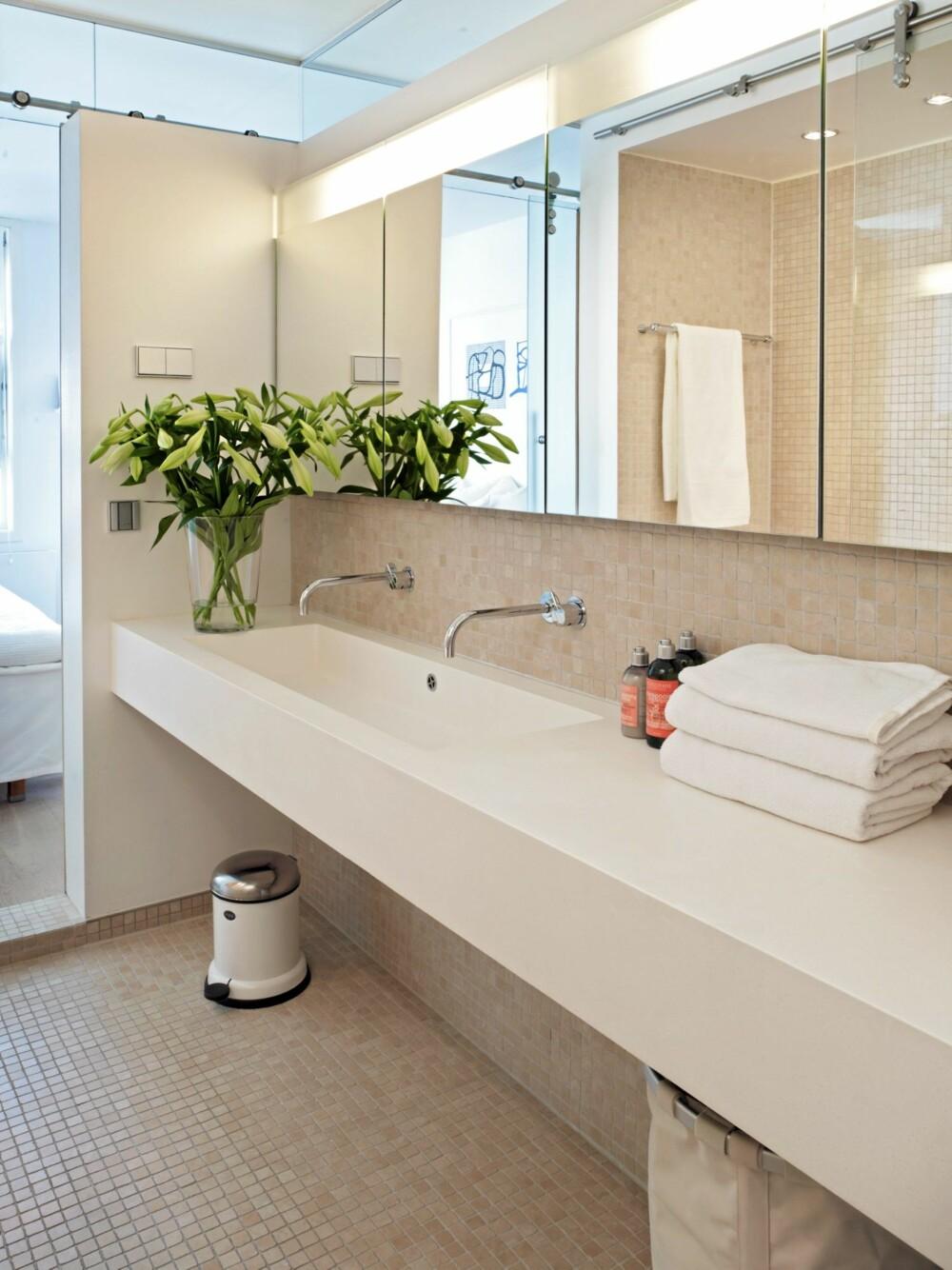 BAD I BOKS. Baderomsinnredningen består av en lang benk, med dobbel vask. Under benken er det helt åpent, og her er det derfor plass til både søppelbøtte og skittentøyskurv. Skapplass finner du derimot bak speilene, som egentlig er skapdører. Gulvet og halve veggen er flisebelagt med beige mosaikk.