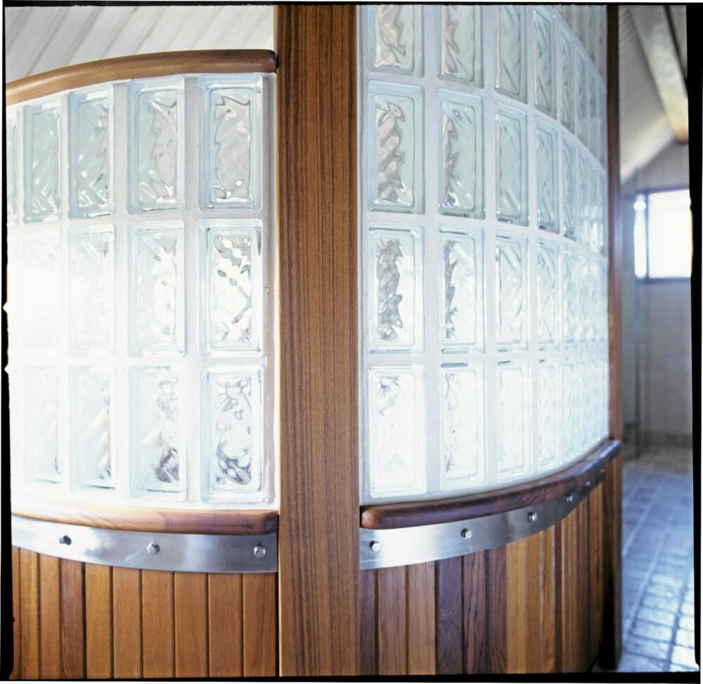 GOD MIKS: Den krumme badekarveggen er avtrappet mot taket og er laget av glassbyggestein, teak og et bredt bånd av rustfritt stål.