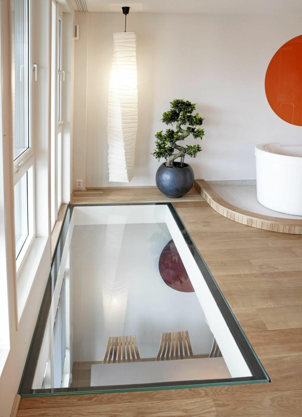 GJENNOMSIKTIG GULV: En to kvm stor glassplate på gulvet øker romfølelsen dramatisk i begge etasjer. Fatet på veggen i etasjen under gjentar «designsirkelen» over badekaret.