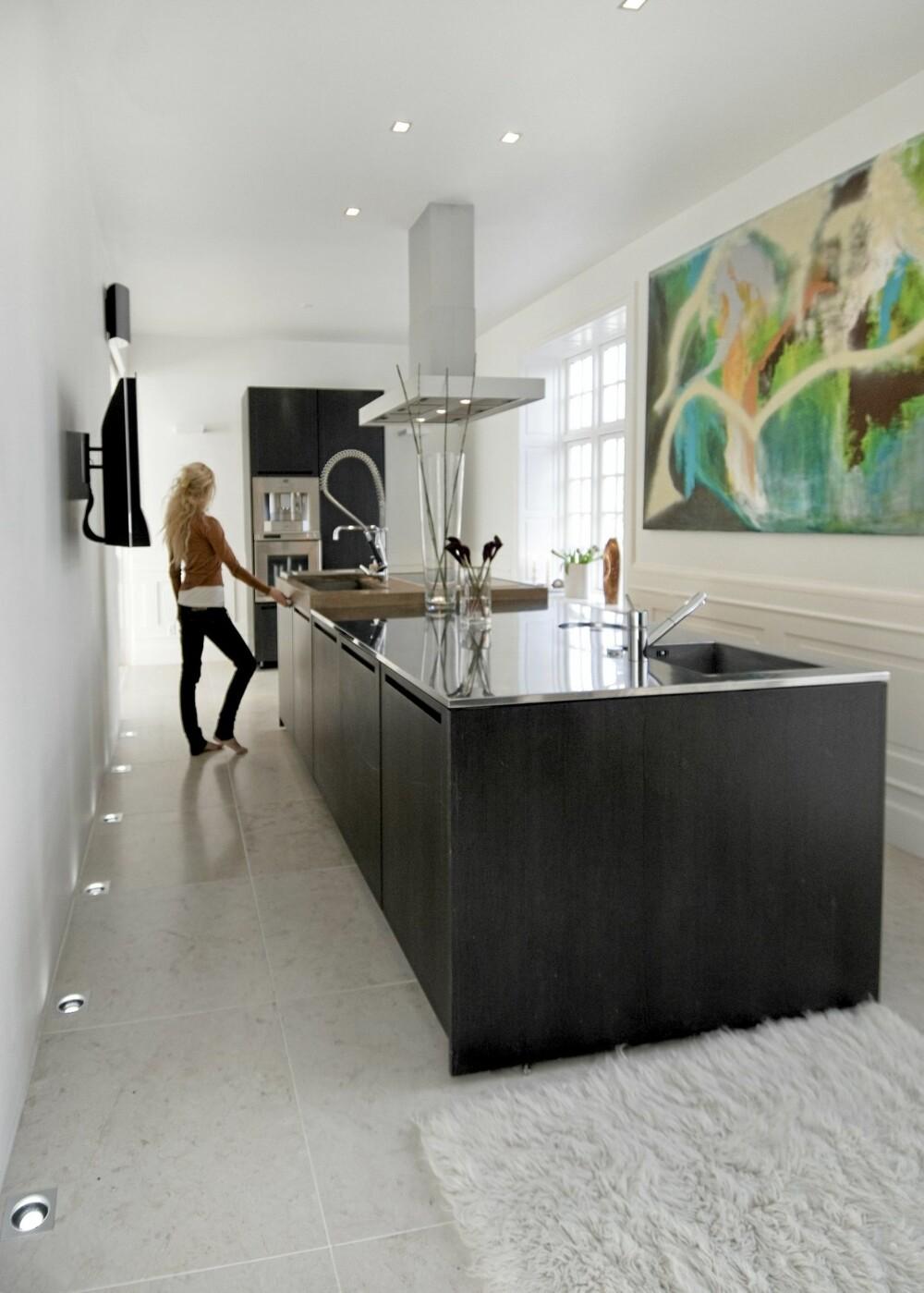 STRAMME LINJER: Mørkbeiset eik står i tydelig kontrast til hvite vegger, gulv og tak. Den fargesterke kunsten er ved William Fabrin, Malunas bror.