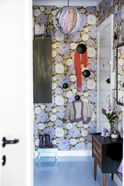 FARGERIK OG STORMØNSTRET: Tapetet er fra Retro Villa, knaggene fra Muuto, mens lampeskjermen er hjemmesydd. Gulvet er malt lyseblått, mens skjenk, speil og veggskap er malt svart.