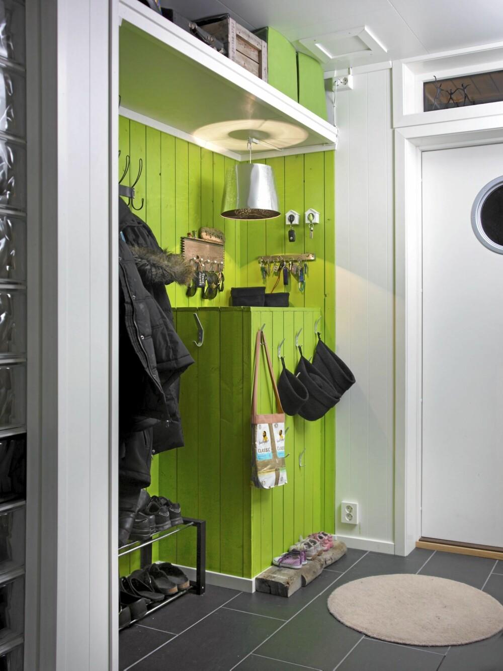 LIMEGRØNT OG REKVED: Veggpanelet er malt i en energigivende grønnfarge. Barneskohylla er et lite stykke rekved fra fjæra.
