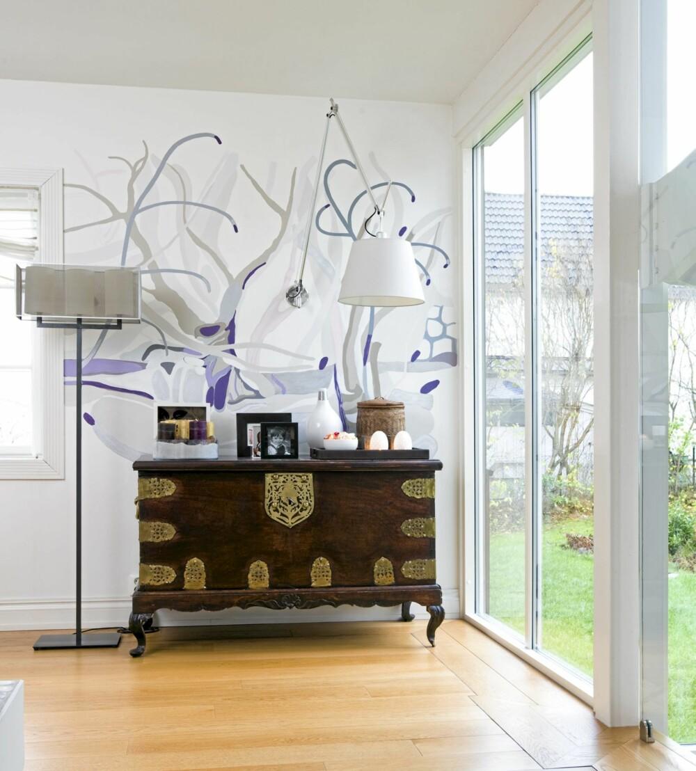 ELEGANT: Miksen mellom antikviteter og ny design er i finstemt balanse og den ti meter lange, dekorerte bakveggen er et syn.