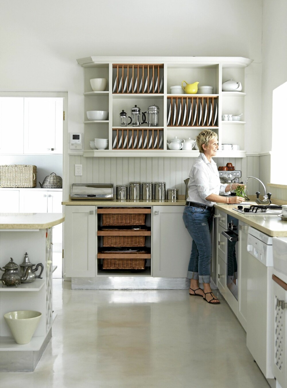 BRUKSSKULPTUR: Det rommelige kjøkkenet er spesialsnekret. Tallerkenhyllene blir nesten til skulpturer med sine sirlig plasserte tallerkener.
