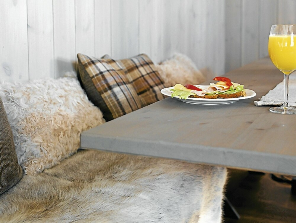 TILPASSET BENK: En lokal møbelsnekker har laget en benk til bordet, og Marianne har sydd putene.