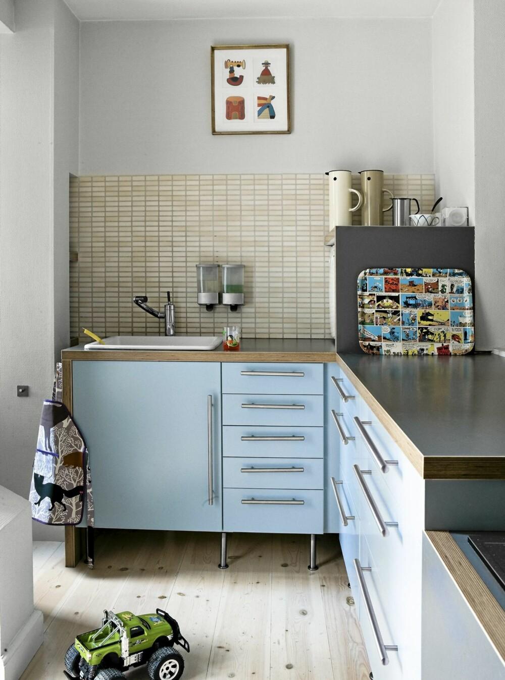 kJØKKEN: Kjøkkenet  fra Ikea ble spesialtilpasset av en møbelsnekker. Den grå kassen på kjøkkenbenken er en innebygd oppvaskmaskin. Serveringsbrettet er kledd med Lucky Luke-tegneserier og lakkert med gulvlakk.