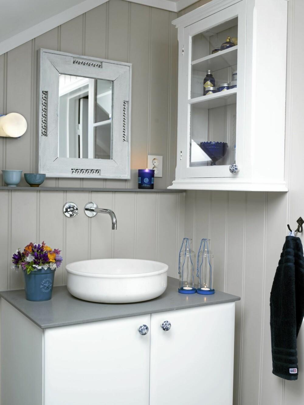 BLE LYSERE: Det nye badet er lyst med hvite, beige og grå detaljer. Servanten fra Tjersland&Co er i marmor og har samme form som et gammeldags vaskefat. Servantskapet fra Kvik har blåblomstrede porselensknotter fra Home&Cottage. Blå håndklær og blomsterpotte er fra Lexington, grått håndkle og lykter er fra Jotex.