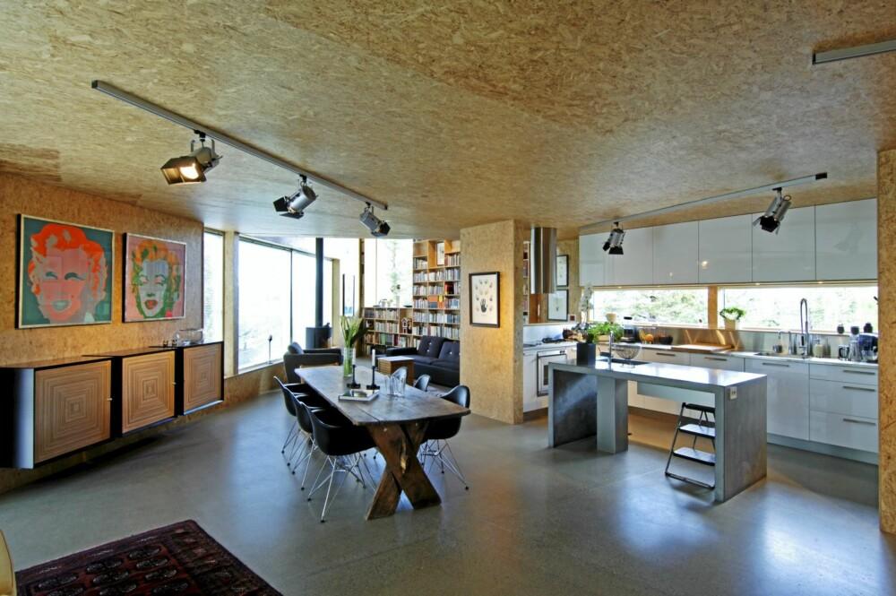 OVERSIKT. Her se vi hvordan og kjøkken og stue henger sammen. Den uvanlige materialpalletten med pusset betonggulv mot sponplater er en utmerket match.
