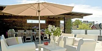 """BEHAGELIG UTEPLASS. Terrassen har plass til både salong og utekjøkken. Utemøblene """"Bubble Club"""", design Philippe Starck, kan stå ute hele året, men skyves likevel under tak om vinteren."""