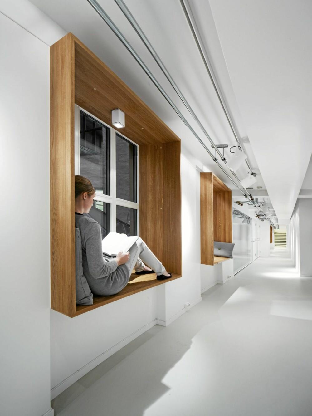 Her var utfordringen å gjøre en lang, smal gang til nytteareal, derfor ble eikeboksene med leselys montert på veggene. Der kan ansatte jobbe på laptoper eller for eksempel lese.
