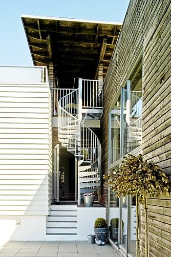 SVINGTRAPP. Fra husets kjøkkeninngang er det kort vei opp trappen til terrassen. Overbygget sørger for at man går tørrskodd i uansett vær.