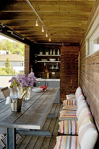 GJESTFRITT. Det lange bordet og benken er bygd av en snekker. 14 stykker kan benke seg rundt spisebordet. Bordet er lagd av samme planker som ligger på gulvet. De røffe bordbeina er smidd sammen av H-bjelker i stål.