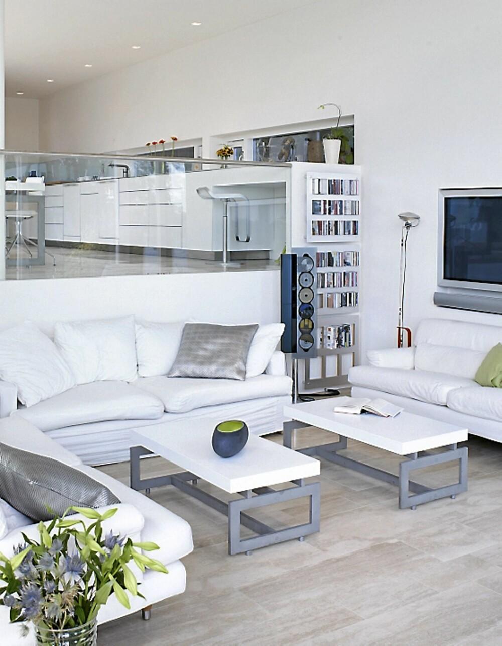 """NIVÅFORSKJELL: Kjøkken og stue kjennetegnes av åpenhet og nærhet mellom rommene. Sofaene """"Cicero"""" fra Erik Jørgensen, bordene er tegnet av arkitekt Ramfelt og musikkanlegg fra Bang og Olufsen på Skøyen."""