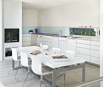 VELUTSTYRT: Kjøkkenet med spiseplass er minimalistisk, men innholdsrikt. Gasspeis fra Heat & Glo, glassvegg med LED-belysning innfelt i veggpartiet. Kjøkkeninnredningen er fra Bulthaup, spisebord og salongbord er utført i sandblåst stål med Corian bordplater tegnet av Ramfelt. Stolene «Catifa» fra italienske Arper.