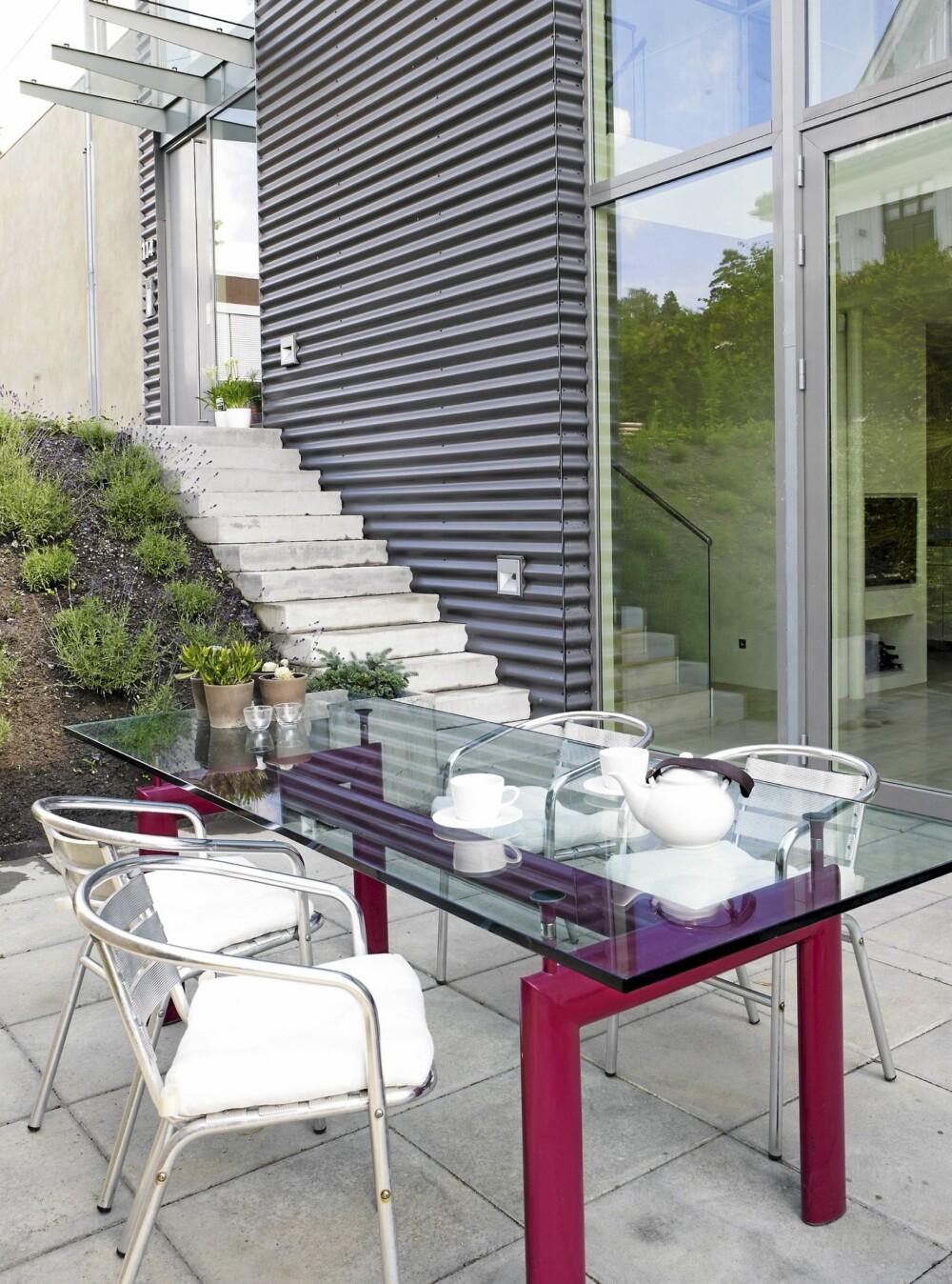 UTEPLASSEN: Utenfor kjøkkenet ligger spiseplassen for de varme sommerdagene. Glassbordet er tegnet av Le Corbusier og stolene er fra Ikea.