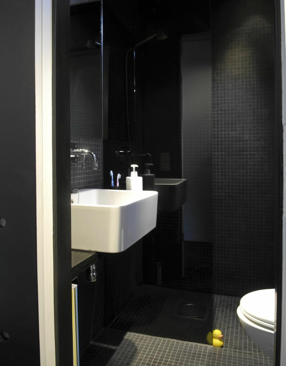 SVART OG KOMPAKT: En halvvegg av frostet, sotet glass separerer dusjen innerst fra toalett og servant ytterst.