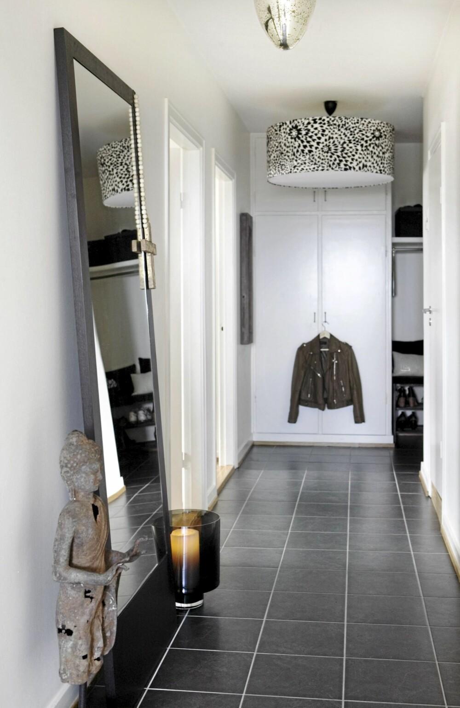 VELKOMMEN: Et gedigent speil stående på gulvet gjør at gangen virker større. Lampen fra Missoni er et blikkfang, det samme er skulpturen. Gulvfliser fra Flisekompaniet.