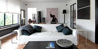 TIDLIGERE SMIE: Den digre stua i svart og hvitt befinner seg i en renovert kunstsmie utenfor den belgiske byen Lier. Beboerne samles i sofaen for å se film fra en projektor som er montert i himlingen. Bildet er tatt av den flamske fotografen Marc Lagrange og har navnet Rwanda Girl.