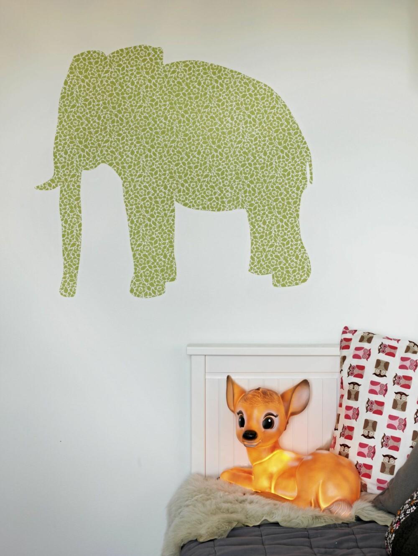 DYRELIV OG RØRE: Et stort elefantklistremerke er klippet ut av en tapetrull fra Tapetorama, og festet på veggen. Sammen med en bambilampe i plast og et hjemmesydd ugleputetrekk bidrar dette til å skape barnevennlige omgivelser.