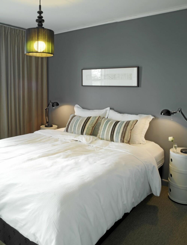 EGEN SUITE: Veggen er malt i skyggeblå fra Jotuns Pure Color. Vegg-til-vegg-teppet Fletco sisallike fra interiorkupp.no og lange, tette gardiner fra Ikea skaper hotellfølelse på soverommet. Taklampen er fra Habitat, bordlampene fra Ikea og nattbordene fra Kartell.