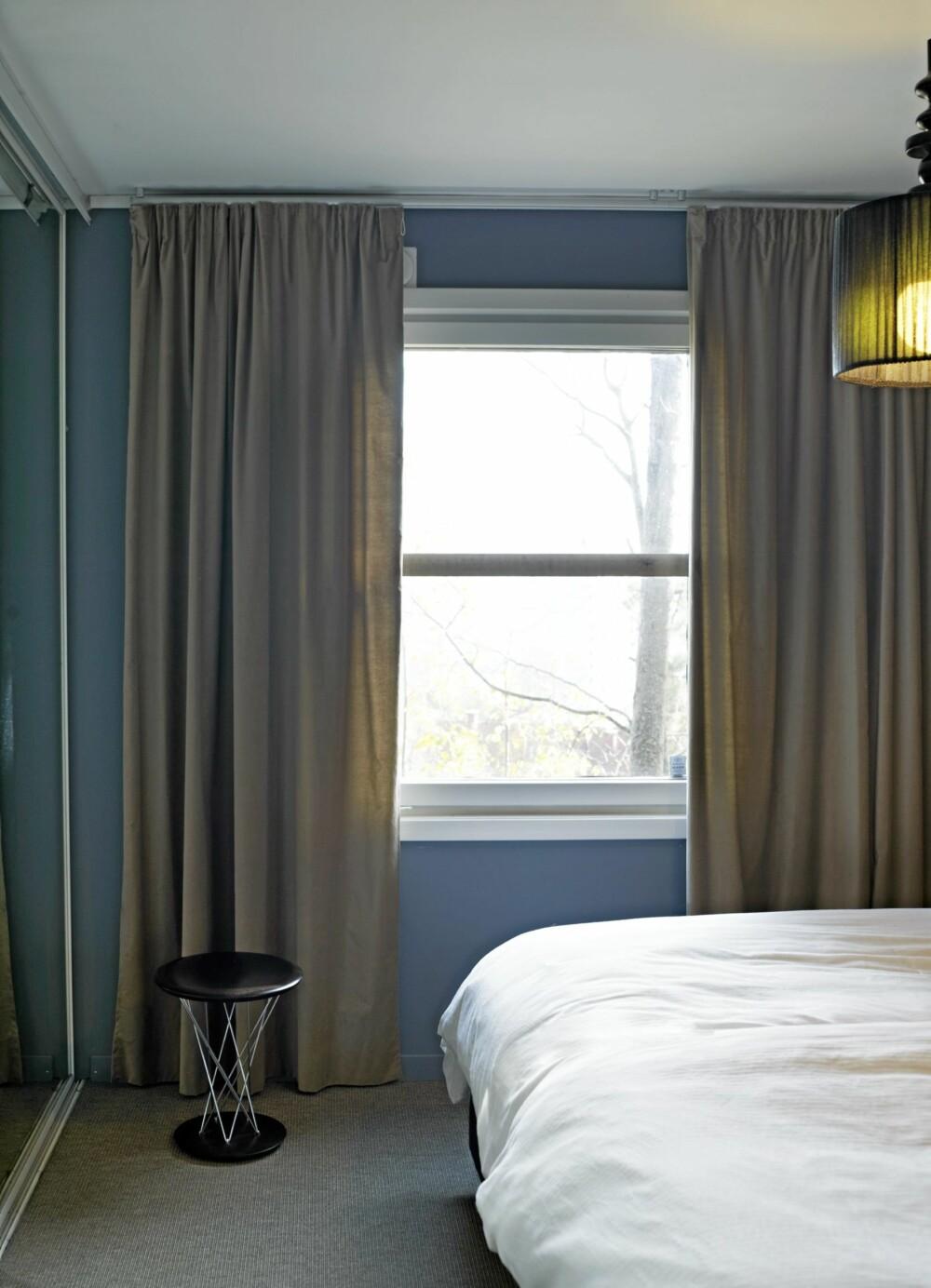 FORSTØRRER VINDUET: Gardinene dekker veggene på hver side av vinduet. Slik kan man forledes til å tro at vinduet egentlig er større enn det er. Gyngekrakken er fra Vitra.