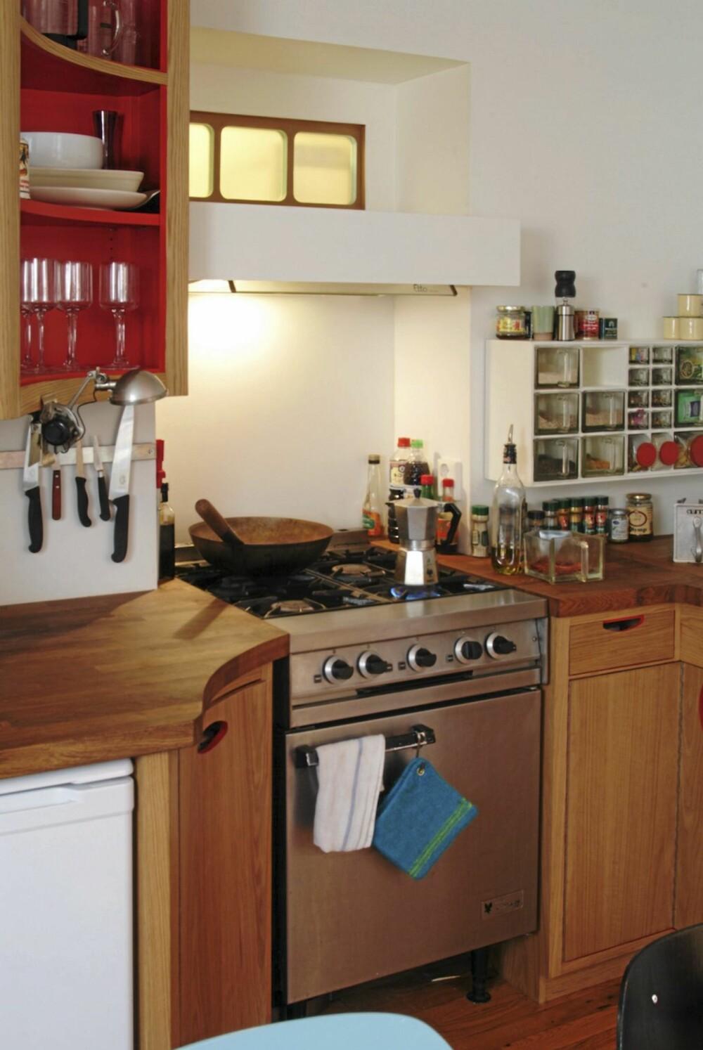 KULT KJØKKEN: Eieren snekret et kjøkken i massiv eik til den nyoppussete leiligheten. Legg merke til de kraftige dimensjonene og de røde kontrastfargene i deler av innredningen. En rekke små vinduer av frostet glass gir lys i rommet rett bak skilleveggen.
