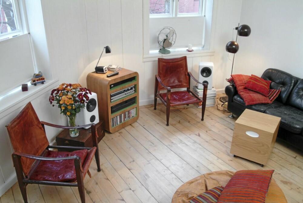 OVERSIKT OVER STUEN: Her ser du hvordan møblene i rommet, de to Safari-stolen og salongbordet designet av huseieren spiller sammen. Musikkhyllen ved vinduet er også Al Coulsons verk.