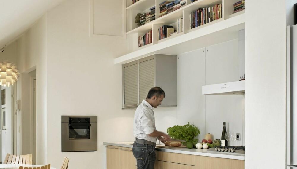 OPPHØYET LITTERATUR: Bøkene er plasser i to meters høyde over gulvet. Kjøkkenet fra Bulthaup består av benkeskap med fronter i lys valnøtt og veggskap med rulleskrogsfronter i stål. Veggplatene over benken er i laminat.
