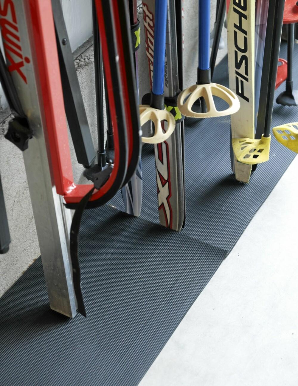 GUMMIMATTE. En gummimatte er delt i to fungerer som underlag for skiene. Da blir de ikke ødelagt under lagring eller når de taes inn og ut gjennom vinteren.