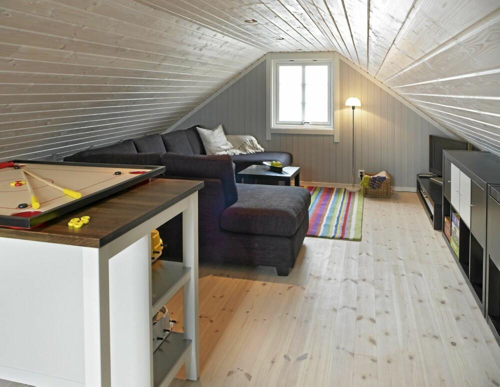 LAVT UNDER SKRÅTAKET. Oppholdsrommet regnes ikke som boligrom og det er kun 1,87 meter under taket. Plassen under skråtaket er godt utnyttet, også bak sofaen er det oppbevaringshyller. Furugulvet fra Siljan er hvitvokset.