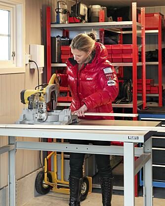 FINGERFERDIG. Helle Huseby ved arbeidsbord fra Norlag. Bordplaten er i stål, den er stabil og lett å holde ren. Bordet er justerbart slik at det passer for hele familien. I vinterhalvåret får hagebordet plass under benken.