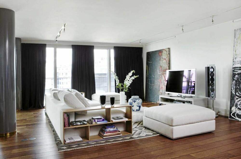 STORE VINDUER: Vinduene fra gulv til tak går langs hele veggen. Gardiner i mørk gråblå fløyel fra JAB. Puff og sofa med integrert hylle fra Magazin. Eierne har gjort det til et bevisst valg å tone ned rødfargen i gulvet ved hjelp av gardiner og møbler.