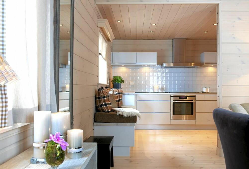 ET STED FOR DIALOG: Kjøkkenet like ved stuen byr blant annet på rause kjøleskuffer og en hyggelig sittebenk. Nordby Snekkerverksted, Øyer var produsent av det meste av fast innredning i hytta.