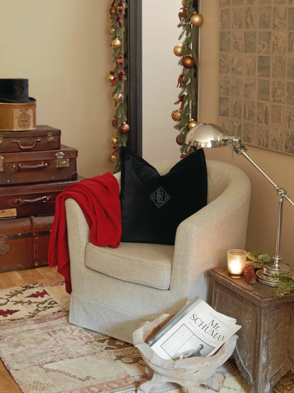 FIIN BLANDING: Kunstig granbar henger rundt dørkarmen, pyntet med julekuler og røde sløyfer. Gamle kofferter er plassert oppå hverandre på gulvet ved siden av den lille lesekroken.