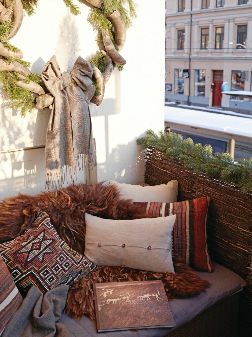BALKONGEN: Den lille balkongen har plass til to modulstoler fra Ikea og et lavt bord. Med lave møbler sitter man mer skjermet for vind og innsyn. En ruvende krans i horn er pyntet med et vanlig ullskjerf og piletre. Kelimputer fra Celine Maktabi, lys linpute fra Konzept HP, og saueskinn fra Palma.