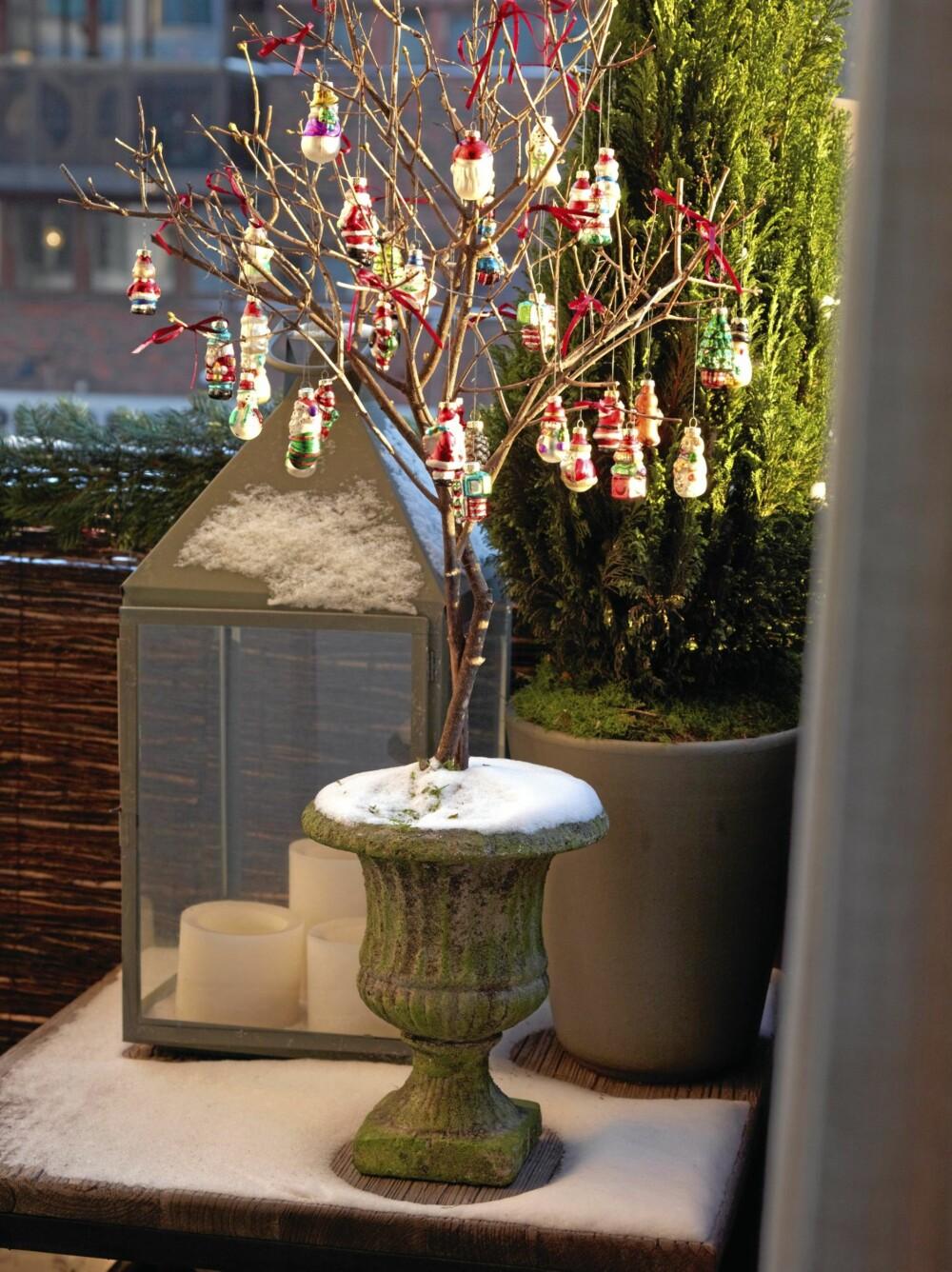 UTEHYGGE: Et grønt tre, en stor lykt og pyntede grener skaper jul på balkongen. Lykten er fra Christian's. De røde figurene minner litt om gammeldags tysk julepynt, og er kjøpt på Nille.