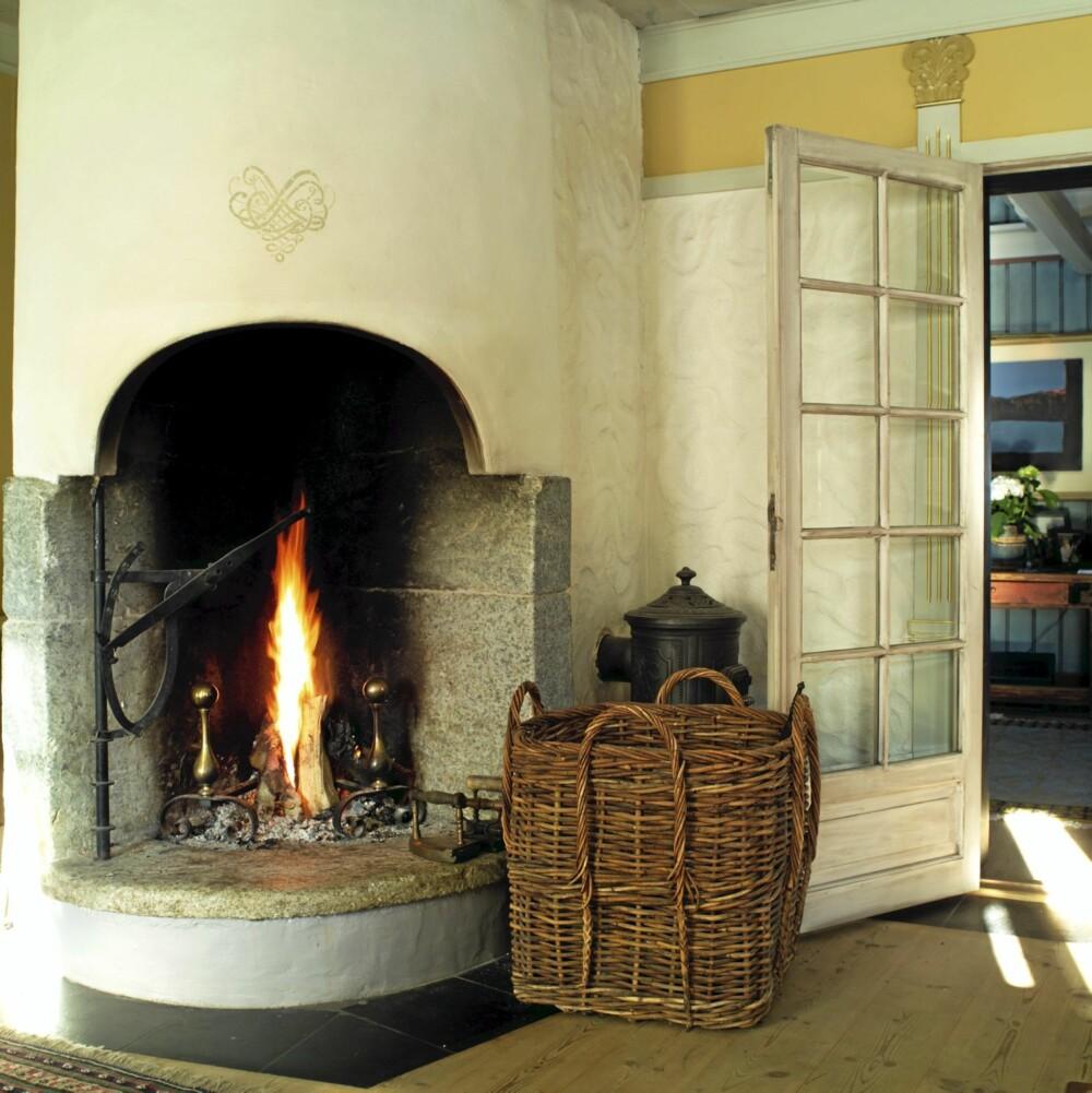 LEKKER LYSOVN: Stuen har en såkalt lysovn, en peistype som var vanlig i Oppdal i gamle dager. Den har en åpning som er stor nok til at den gir lys nok til blant annet håndarbeid. Skinnende dekor signert Lise Skjåk Bræk.