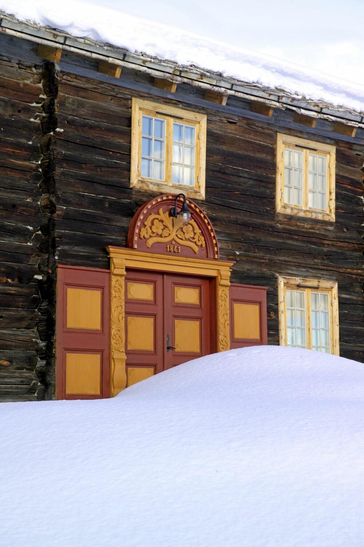 REHABILITERT: Hovedøren på Donalistuggu på Bjerkaker gård har doble dører i gammel stil. Utskjæringene er gjort av en gammel treskjærer på Oppdal.