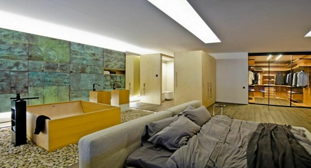 LUFTIG SOVEROM: På soverommet er det ikke mange skiller mellom de ulike funksjonene, så her kan man ikke være sjenert. En glassvegg skiller garderoben fra resten, mens badekaret står midt på gulvet.