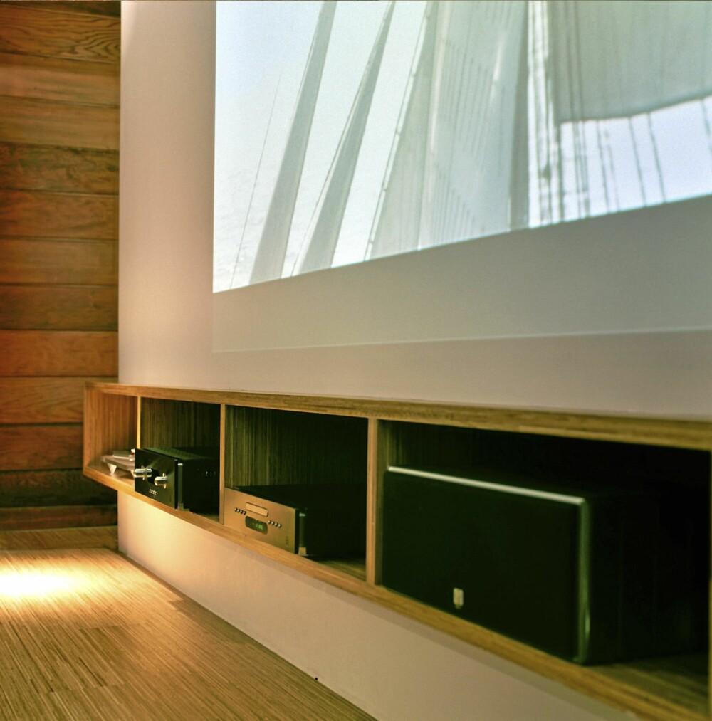 KULE KASSER: Medieinnredningen består blant annet av en lang hylle i eik. For å gi plass til kabler og teknisk utstyr er den foret litt ut fra veggen.
