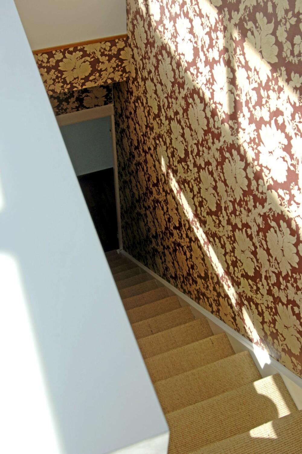 KONTASTER: Sprek trapp mot toppen. Det barokke tapet står i spenstig kontrast til alt det hvite i leiligheten. Sklisikre sisaltepper er gode å ha i slike bratte trapper.