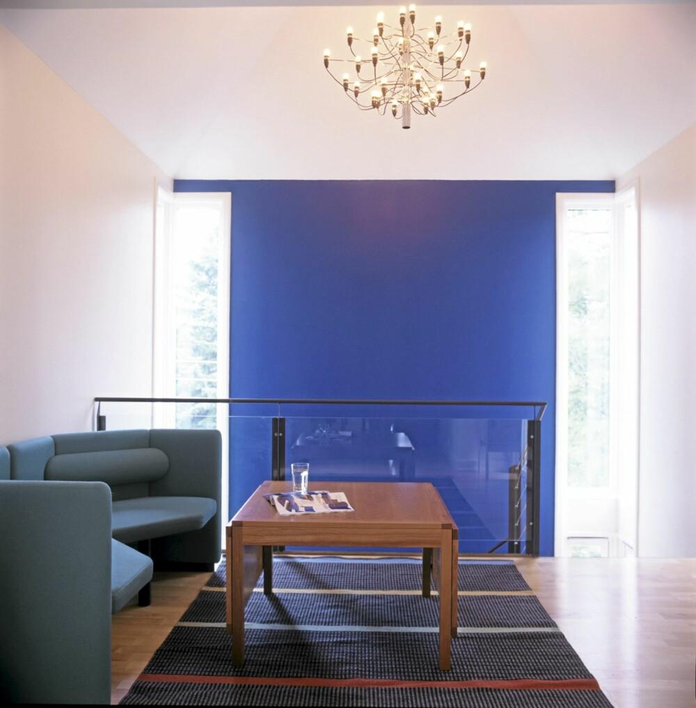 KOBOLTBLÅ KONTRAST: Oppholdrommet/tv-stuen i annen etasje preges også av det koboltblå veggfeltet. Børge Mogensens Fredericia-bord er en av de mange danske designmøblene i huset. I taket en tredve år gammel Flos lampeklassiker. Kasthall gulvteppe.